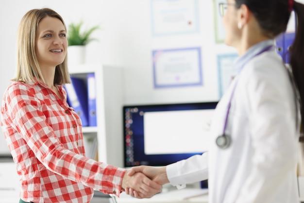 Médico aperta a mão com um conceito de seguro de saúde de conclusão de paciente sorridente