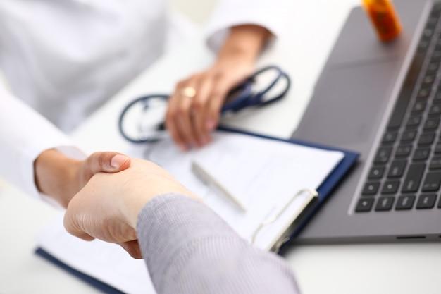 Médico apertar a mão como olá com o paciente