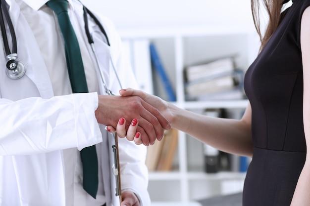 Médico apertar a mão como olá com paciente no escritório closeup