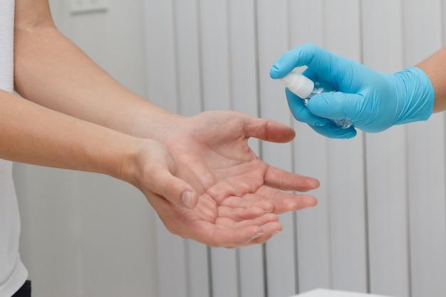Médico aplicando álcool em spray para prevenir a propagação de germes, bactérias e vírus