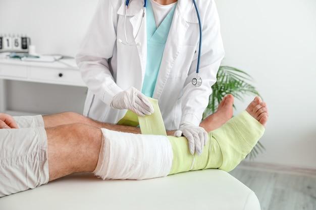 Médico aplicando curativo na perna quebrada de um jovem na clínica