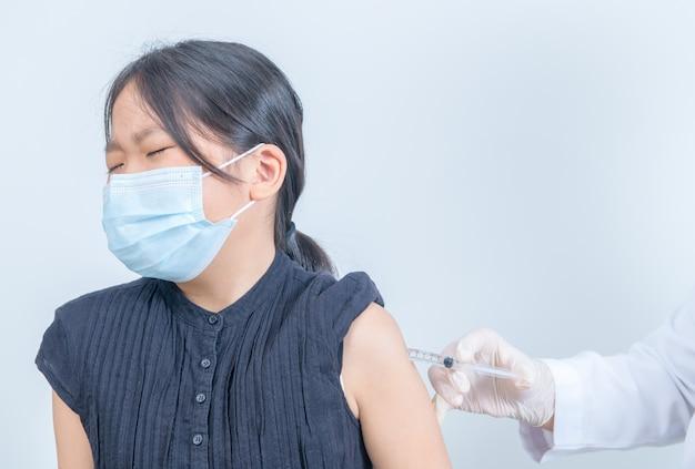 Médico aplicando vacina no braço de uma menina asiática