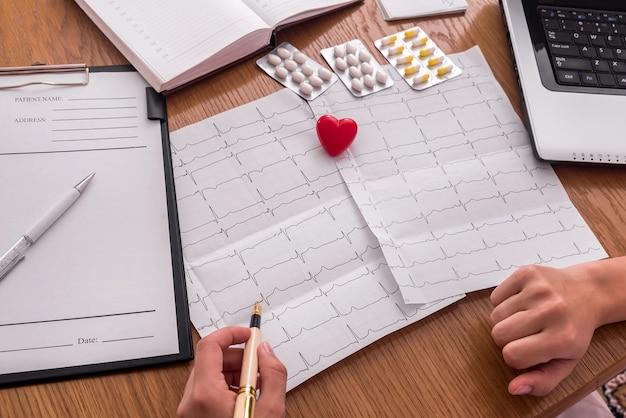 Médico apontando para cardiograma, pílulas e coração vermelho do paciente