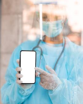 Médico apontando para um smartphone com tela vazia