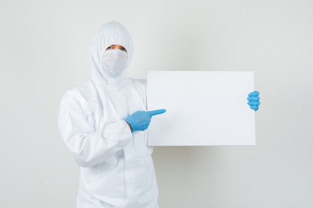 Médico apontando para uma tela em branco em traje de proteção