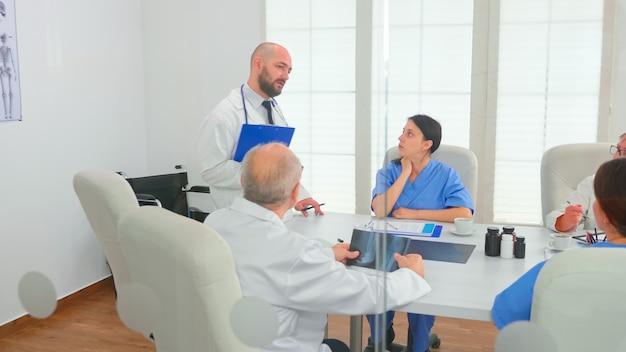 Médico apresentando diagnóstico aos colegas segurando a prancheta durante a reunião com colegas de trabalho. terapeuta especialista em clínica falando com colegas sobre doenças, profissional de medicina