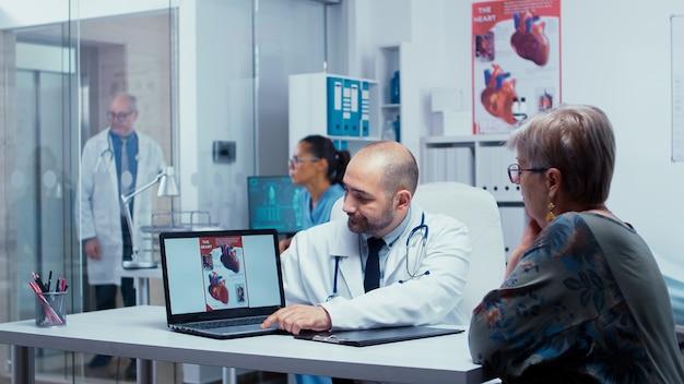 Médico apresentando problemas cardíacos em potencial a paciente idoso, idoso, aposentado. problemas de doença cardíaca apresentados pela cardiologia cardiologista, ligação do coração. cuidados de saúde em clínica privada moderna. equipe médica