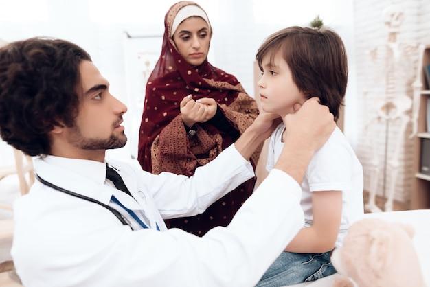 Médico árabe diagnostica um menino pequeno.