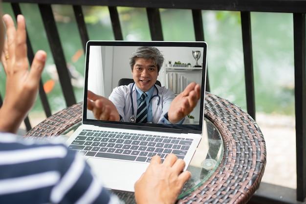 Médico asiático ajuda a aliviar o estresse e fornece conhecimento e compreensão sobre a síndrome do consultório aos pacientes via online