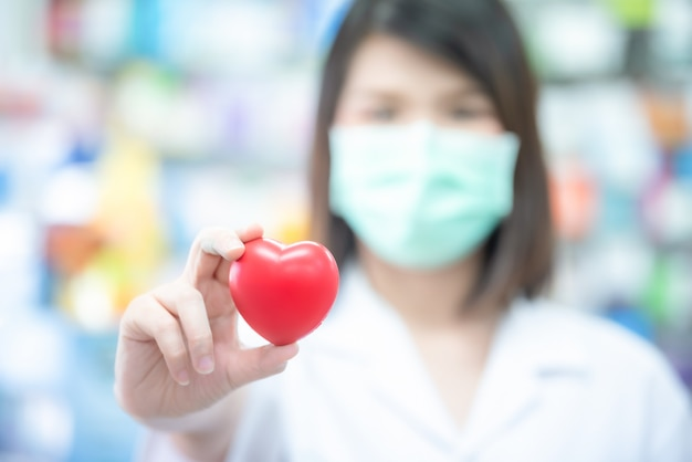 Médico asiático das mulheres que guarda uma bola vermelha do coração com conceito borrado dos cuidados médicos.