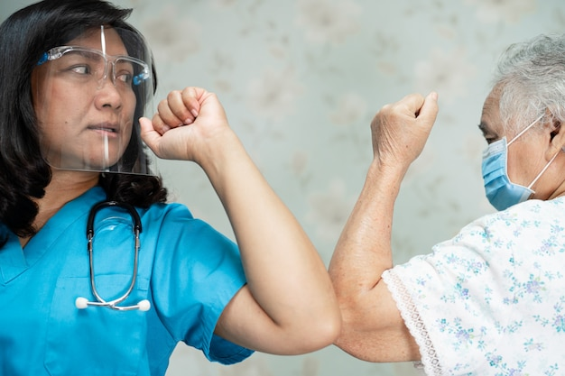 Médico asiático e paciente idoso batem cotovelos por coronavírus covid-19 de distanciamento social