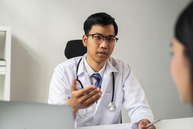 Médico asiático é relatar os sintomas e aconselhar o paciente.