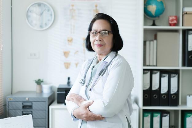 Médico asiático sênior, trabalhando na sala de exame