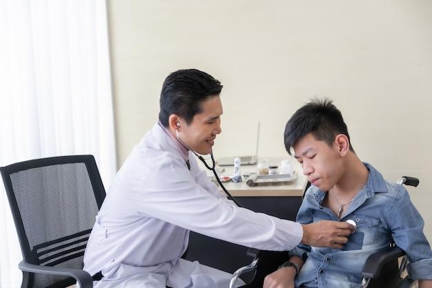 Médico asiático usa estetoscópio para verificar paciente com deficiência física