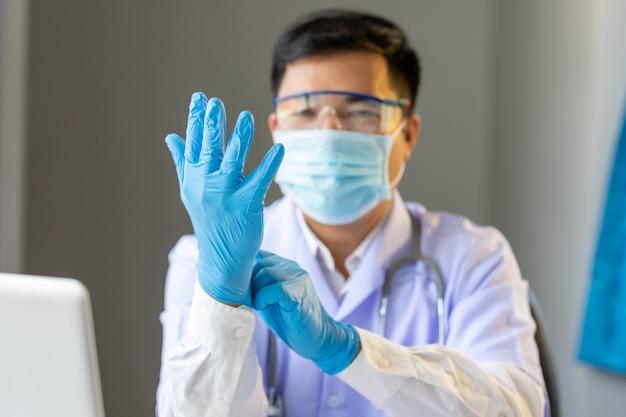 Médico asiático usando luva de proteção para fighting covid-19 (vírus corona)
