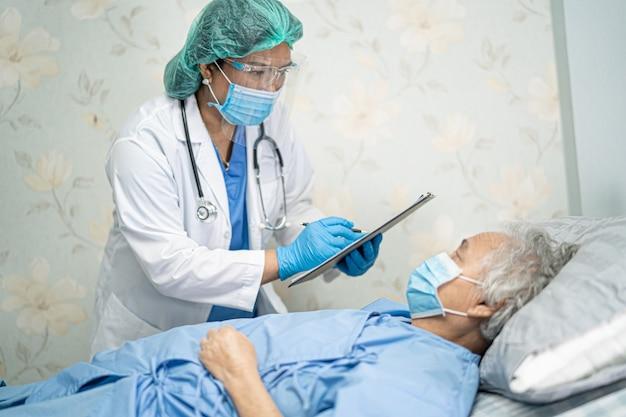 Médico asiático usando protetor facial e traje de epi para proteger o covid-19 coronavirus.