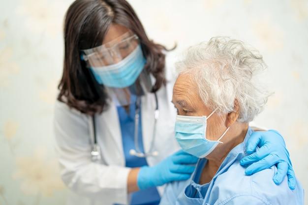 Médico asiático usando protetor facial e traje de epi para verificar a proteção do paciente contra o covav-19 coronavírus.
