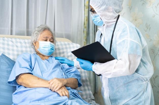Médico asiático usando protetor facial e traje de proteção individual para proteger covid19 coronavirus