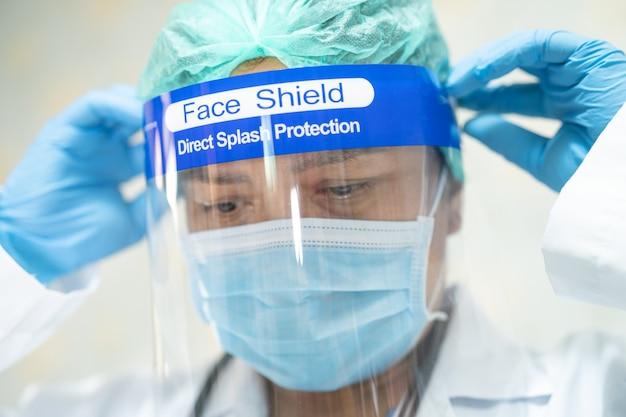 Médico asiático usando protetor facial e traje de proteção individual para verificar a proteção do paciente contra o coronavírus