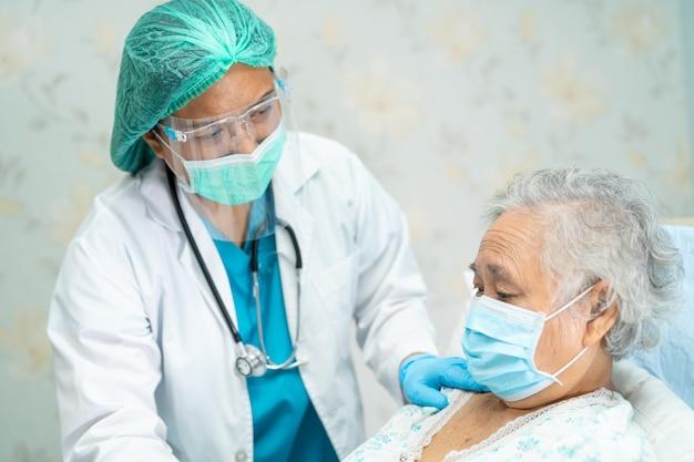 Médico asiático usando protetor facial e traje de proteção individual