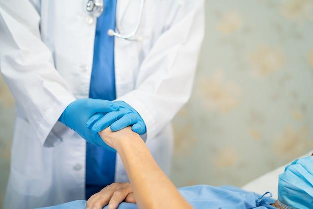 Médico asiático vestindo traje novo de epi normal para verificar paciente com máscara proteger infecção de segurança surto de coronavírus covid-19 na enfermaria de quarentena do hospital.
