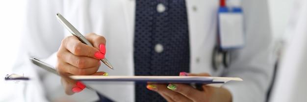 Médico assina o documento com uma caneta esferográfica na reunião com o colega na clínica closeup. descarga do conceito de drogas preferenciais.
