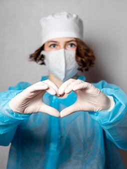 Médico assistente em uma máscara descartável e um jaleco faz um sinal de coração.