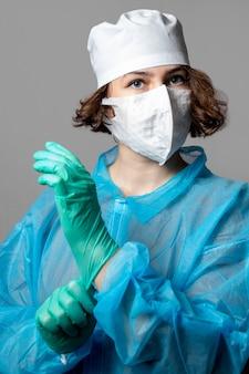 Médico assistente em uma máscara descartável e um jaleco