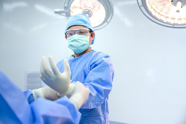 Médico assistente ou cirurgião masculino está usando luvas para o médico se preparar para a cirurgia, enquanto está em uma área esterilizada na sala de cirurgia de um hospital