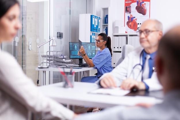 Médico assistente segurando um raio-x sentado no hospital enquanto o médico consulta uma velha em cadeira de rodas. médico fazendo perguntas a uma senhora madura preenchendo formulário de histórico de doenças, prescrevendo tratamento