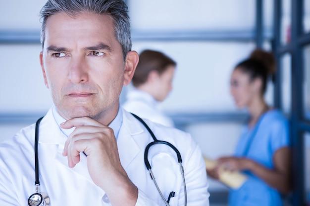 Médico atencioso em pé com a mão no queixo no hospital