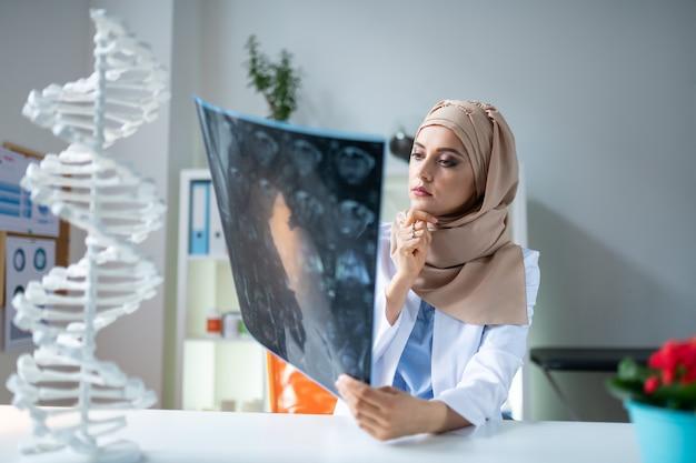 Médico atencioso. médica vestindo uniforme e hijab se sentindo pensativa antes de fazer a receita
