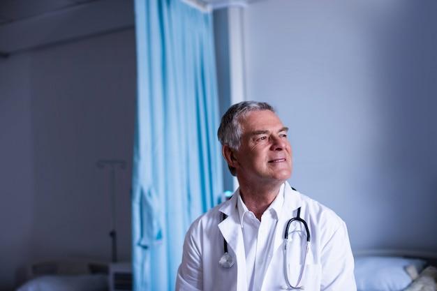 Médico atencioso sentado na enfermaria