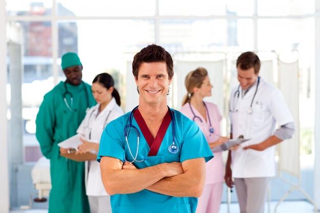 Médico atraente com equipe em segundo plano