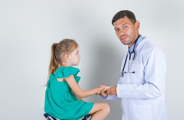 Médico auscultando antebraço de criança em uniforme branco na sala de exame