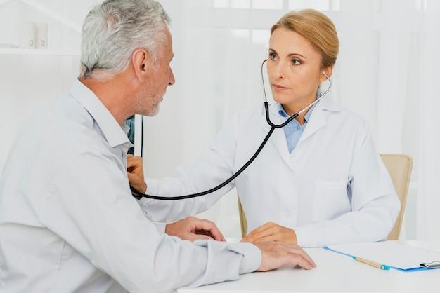 Médico auscultar paciente no peito