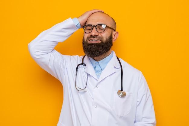 Médico barbudo com jaleco branco com estetoscópio no pescoço e óculos, feliz e animado, sorrindo, segurando a mão na cabeça