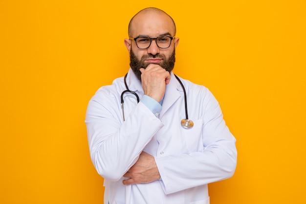 Médico barbudo com jaleco branco com estetoscópio no pescoço e óculos olhando para a câmera com a mão no queixo pensando em pé sobre fundo laranja