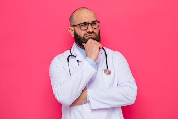 Médico barbudo com jaleco branco com estetoscópio no pescoço e óculos olhando para o lado com a mão no queixo pensando com cara séria em pé sobre fundo rosa