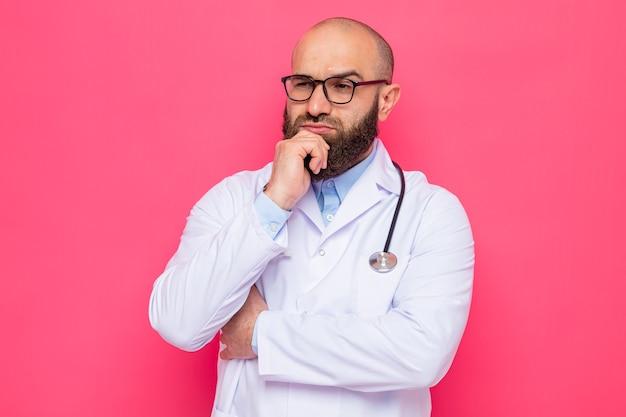 Médico barbudo com jaleco branco com estetoscópio no pescoço e óculos olhando para o lado com expressão pensativa e a mão no queixo pensando