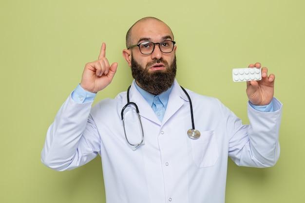 Médico barbudo com jaleco branco com estetoscópio no pescoço e óculos segurando uma bolha com comprimidos apontando com o dedo indicador para cima parecendo surpreso em pé sobre fundo verde