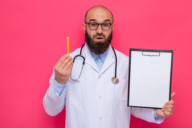 Médico barbudo com jaleco branco com estetoscópio no pescoço usando óculos segurando uma prancheta com páginas em branco e lápis olhando para a câmera surpreso em pé sobre fundo rosa