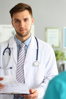 Médico barbudo posando em policlínica