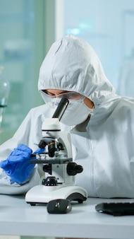 Médico biólogo de macacão, verificando a amostra de dna no microscópio, digitando no pc no laboratório equipado. examinando a evolução da vacina no laboratório médico usando ferramentas de alta tecnologia e química para pesquisa científica