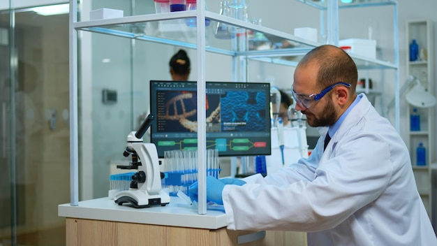 Médico biólogo verificando amostras de dna em um moderno laboratório equipado. equipe multiétnica examinando a evolução da vacina em laboratório médico usando ferramentas de alta tecnologia e química para pesquisa científica.