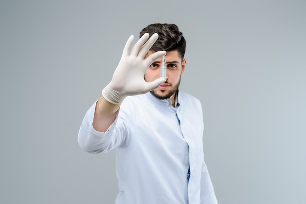 Médico bonitão em luvas segurando uma ampola
