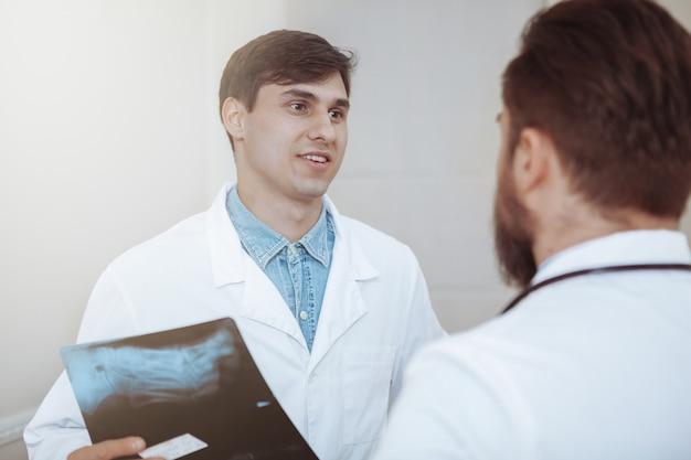 Médico bonitão falando com seu colega, segurando a varredura de raios-x de um paciente.
