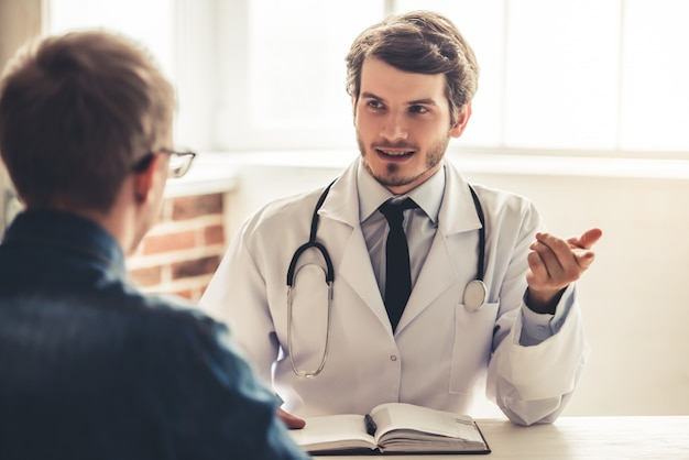 Médico bonitão no jaleco branco está falando com seu paciente.