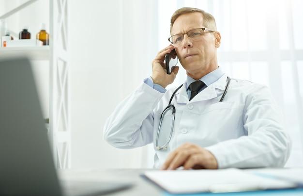 Médico bonito conversando ao telefone na clínica