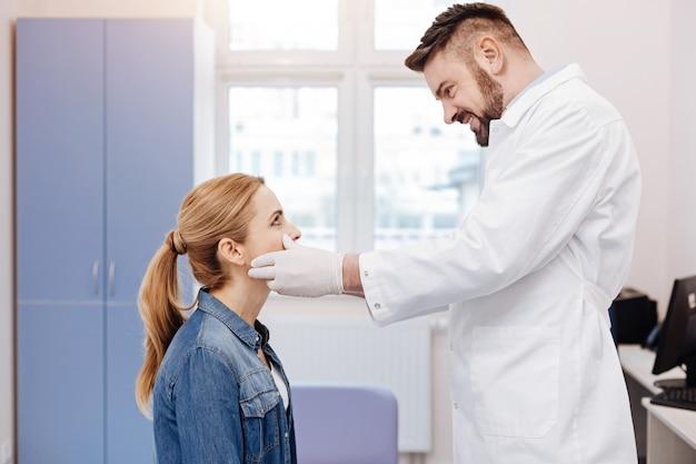 Médico bonito e alegre parado na frente de sua paciente e sorrindo enquanto olha nos olhos dela